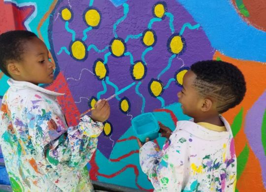 Two boys painting atoms